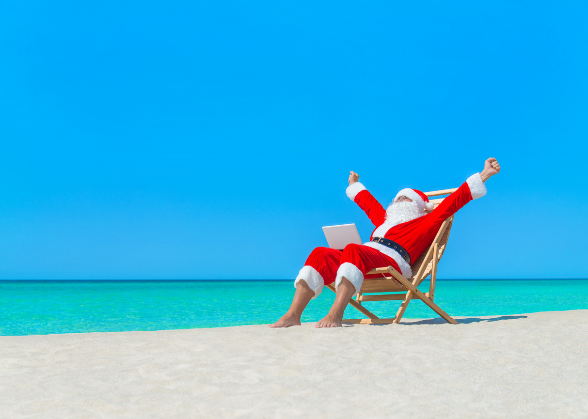 Santa Claus on deck chair hands up enjoy work using laptop computer at ocean sandy tropical beach - Christmas  and New Year vacation and travel destinations in hot countries concept